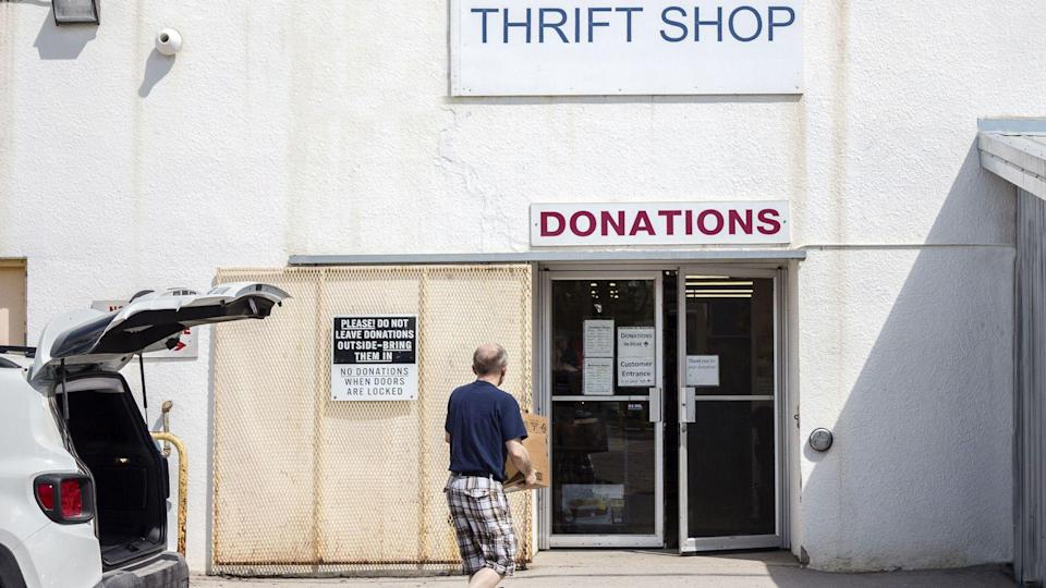 horizontal image of a man carrying donated items into a thrift store .