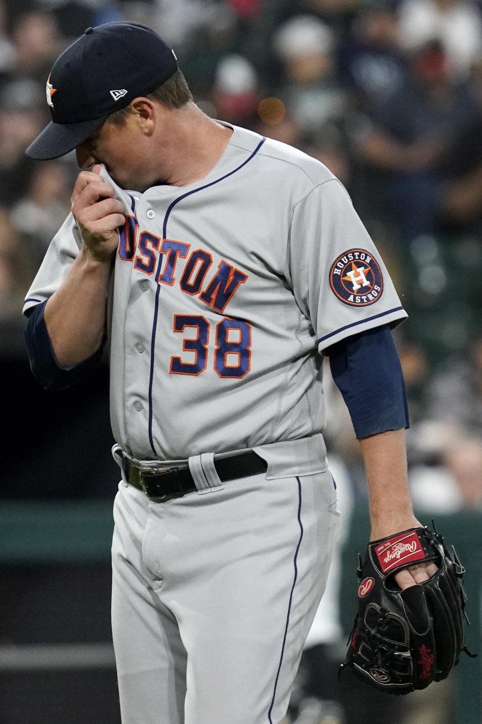 Houston Astros relief pitcher Joe Smith wipes his face as he walks to the dugout after the sixth inning of the team's baseball game against the Chicago White Sox in Chicago, Saturday, July 17, 2021. (AP Photo/Nam Y. Huh)