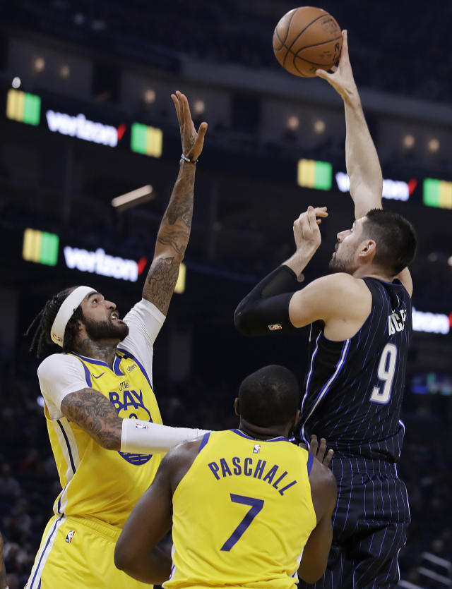 Orlando Magic Nikola Vucevic, right, shoots over Golden State Warriors' Willie Cauley-Stein, left, and Eric Paschall, right, during the first half of an NBA basketball game Saturday, Jan. 18, 2020, in San Francisco. (AP Photo/Ben Margot)