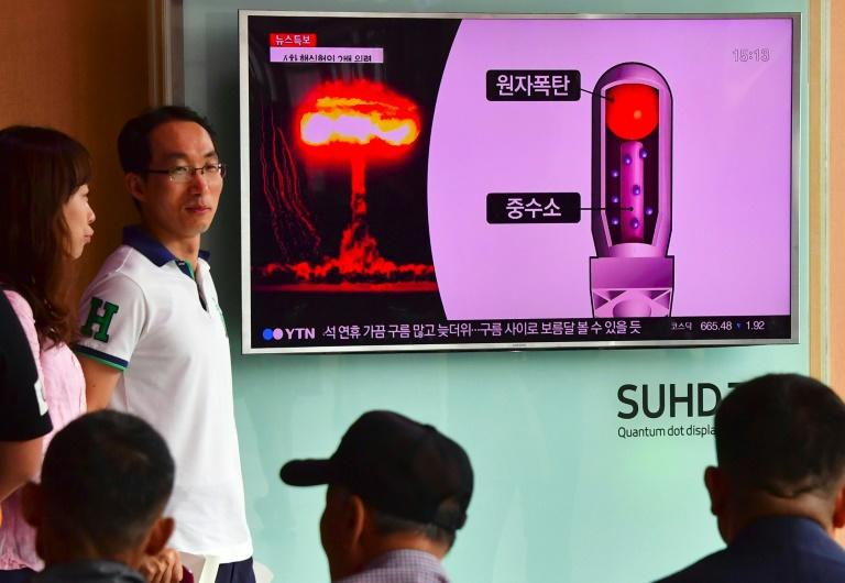 People watch a television news report on North Korea's latest nuclear test, at a railway station in Seoul, on September 9, 2016