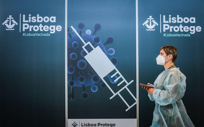 A healthworker walks by a poster at a Covid-19 vaccination center in Lisbon on July 2, 2021. - Nearly half of Portugal's population will be placed under night-time curfews again from Friday as the government seeks to rein in a resurgence in coronavirus infections, primarily due to the more contagious Delta variant. - AFP