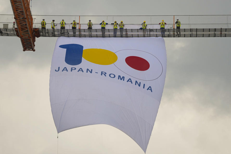 Workers stand during a ceremony marking 100 years of diplomatic relations between Japan and Romania, at the construction site of a suspension bridge over the Dnube river in Braila, Romania, Thursday, Aug. 26, 2021. The bridge, built by Japanese and Italian companies, with a span of 1,974.3 meters, will be the largest of its kind in Romania and the third in the European union.(AP Photo/Vadim Ghirda)