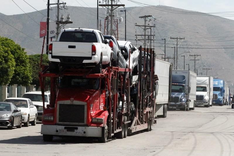 A car carrier transports Toyota trucks for delivery while waiting in queue for border customs control to cross into the U.S., at the Otay border crossing in Tijuana