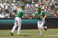 Oakland Athletics' Ramon Laureano is greeted by third base coach Mark Kotsay after hitting a home run in the fourth inning of a baseball game Wednesday, June 16, 2021, in Oakland, Calif. (AP Photo/Eric Risberg)