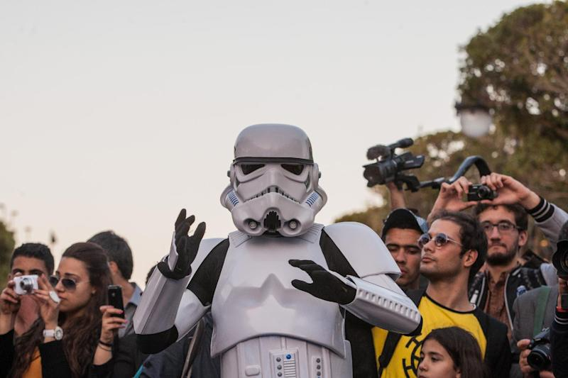 "A Star Wars fan wearing a stormtrooper costume parades along Tunis' stately, tree-lined Bourguiba Avenue, in Tunisia, Wednesday, April 30, 2014. The empire was not striking back against the poster child for Arab democracy — just an innovative campaign to encourage tourists to return to this sunny desert-and-beach nation in North Africa. ""We came here to Tunis to help save the Star Wars sites in Matmata and Tozeur and convince people to return to Tunisia,"" said Ingo Kaiser, head of a Star Wars fan club in Europe, referring to the movie sets that are slowly being covered up by sand in the Tunisian desert. (AP Photo/Aimen Zine)"