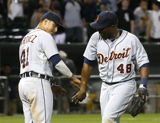 Detroit Tigers' Victor Martinez (41) celebrates with right fielder Torii Hunter the Tigers' 7-3 win over the Chicago White Sox after a baseball game Monday, July 22, 2013, in Chicago. (AP Photo/Charles Rex Arbogast)
