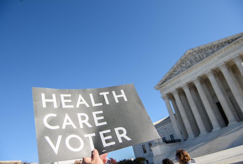 """A demonstrator holds a sign in front of the US Supreme Court in Washington, DC, on November 10, 2020, as the high court opened arguments in the long-brewing case over the constitutionality of the 2010 Affordable Care Act, under which then-president Barack Obama's government sought to extend health insurance to people who could not afford it. - President Donald Trump's outgoing administration took aim in the US Supreme Court Tuesday at razing the """"Obamacare"""" health program his predecessor built, a move which could cancel the health insurance of millions in the middle of the Covid-19 pandemic. (Photo by NICHOLAS KAMM / AFP) (Photo by NICHOLAS KAMM/AFP via Getty Images)"""