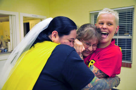 Kathy Voigtschild (L) and Rachel Baker (R) embrace Rachel's mother Debra after getting married at Mayflower Congregational Church in Oklahoma City, Oklahoma October 6, 2014. REUTERS/Nick Oxford
