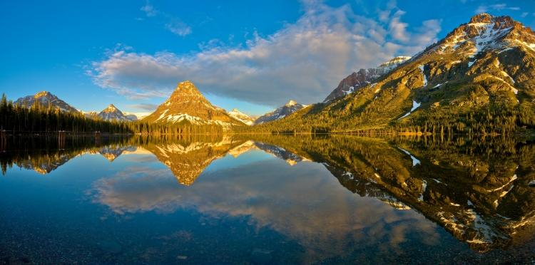 Glacier National Park, MT - Early morning provided a mirror-like reflection on Two Medicine Lake as the rising sun catches the mountains surrounding the lake. © World Wildlife Fund/Mike Walker
