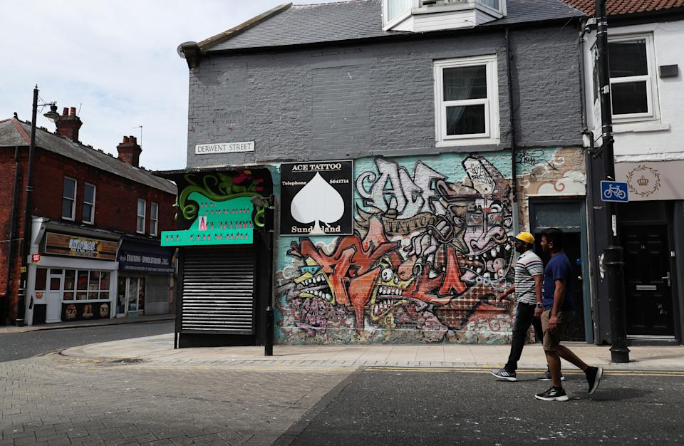 People walk past a closed Tattoo studio in Sunderland, following the outbreak of the coronavirus disease (COVID-19), Sunderland, Britain, June 2, 2020. REUTERS/Lee Smith