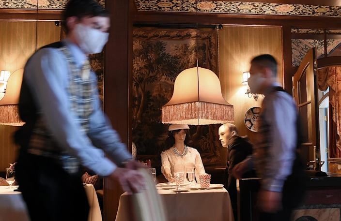 """<h1 class=""""title"""">US-HEALTH-VIRUS</h1> <div class=""""caption""""> Servers wear face masks as they pass mannequins populating the dining room of The Inn at Little Washington, in Washington, Virginia, on the first day of Virginia's Phase 1 reopening. </div> <cite class=""""credit"""">Photo: OLIVIER DOULIERY/AFP via Getty Images</cite>"""