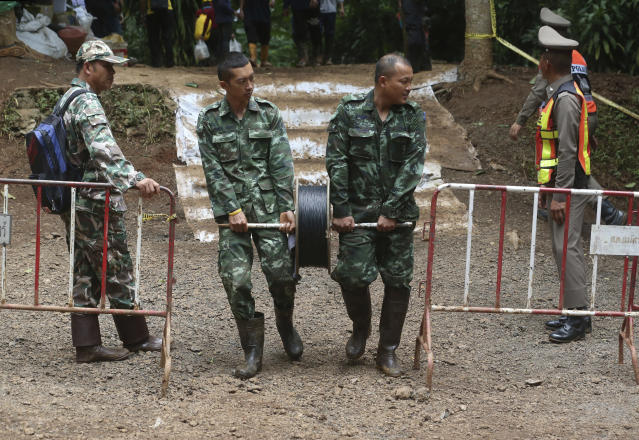 <p>Rescuers lay telephone cable from a cave where a young soccer team and their coach were trapped Thursday, July 5, 2018, in Mae Sai, Chiang Rai Province, northern Thailand. (Photo: Sakchai Lalit/AP) </p>