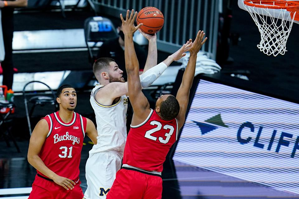 Michigan center Hunter Dickinson shoots between Ohio State forwards Seth Towns, left, and Zed Key in the first half of the Big Ten tournament semifinal in Indianapolis on Saturday, March 13, 2021.