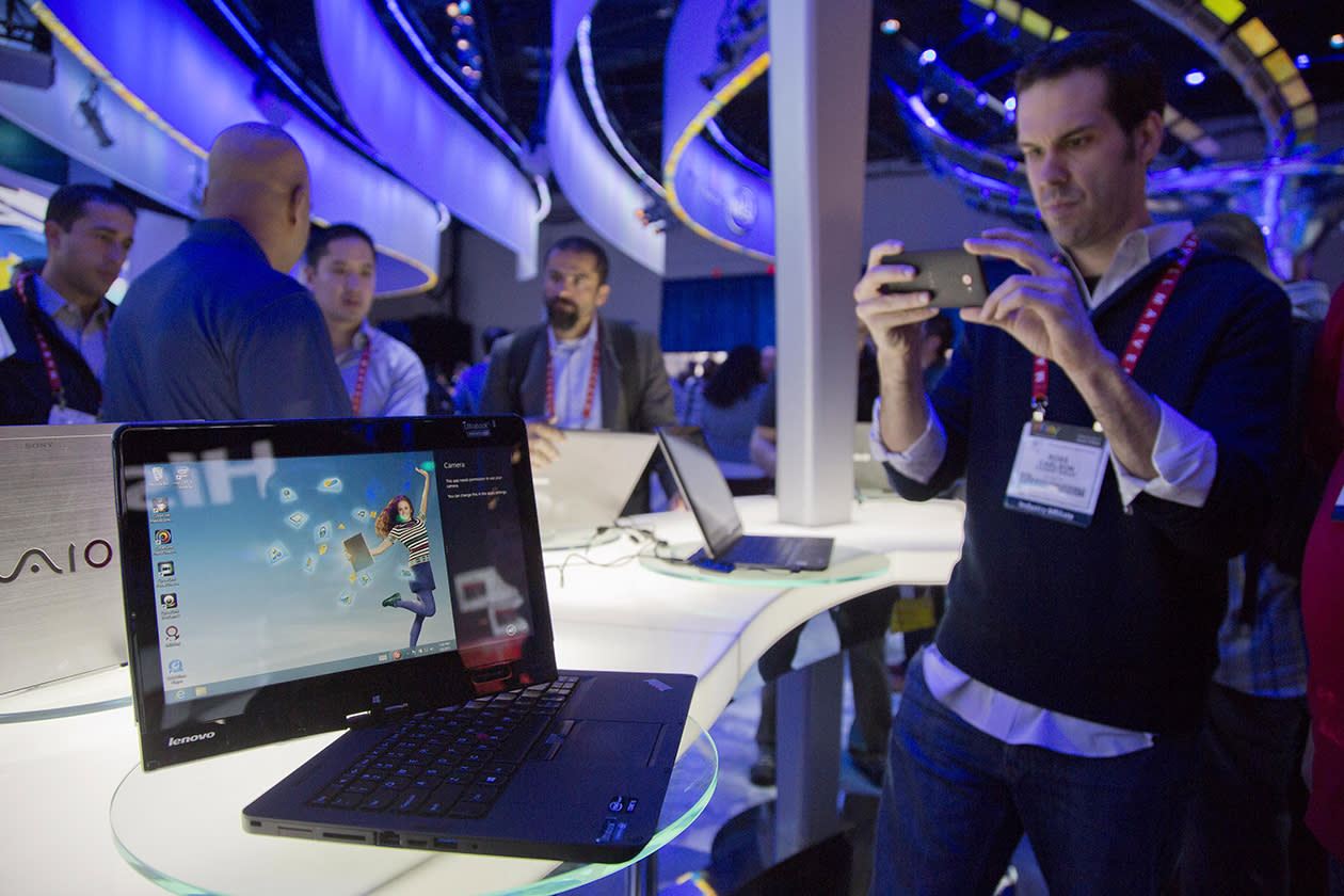 Convention goers photograph a Lenovo convertible Ultrabook at the Consumer Electronics Show.