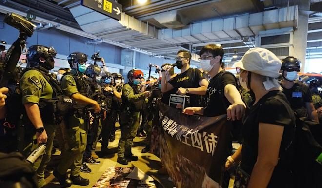 Democratic Party lawmaker Lam Cheuk-ting (centre) at a rally marking the first anniversary of the Yuen Long attack, surrounded by police officers. Photo: Felix Wong