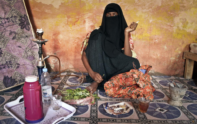 In this photo taken Tuesday, Sept. 18, 2012, prostitute Faduma Ali, who longs for the days when her pirate customers had money, chews the stimulant khat and smokes a cigarette at a house in the once-bustling pirate town of Galkayo, Somalia. The empty whisky bottles and overturned, sand-filled skiffs that litter this shoreline are signs that the heyday of Somali piracy may be over - most of the prostitutes are gone, the luxury cars repossessed, and pirates talk more about catching lobsters than seizing cargo ships. (AP Photo/Farah Abdi Warsameh)