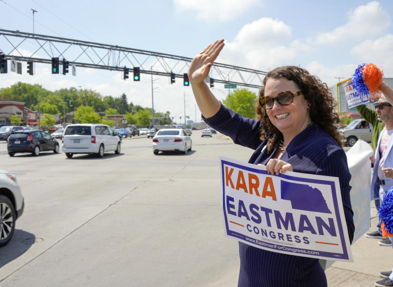 Democratic House candidate Kara Eastman waves to passing motorists in Omaha, Neb., Tuesday, May 15, 2018. Eastman is running against Democrat Brad Ashford in Tuesday's primary election, and the winner will challenge U.S. Rep. Don Bacon, R-Neb., after the congressman claimed the seat from Democrats two years ago. (AP Photo/Nati Harnik)