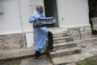 A researcher for Brazil's state-run Fiocruz Institute, wearing protective gear, transports captured monkeys to a holding area, at Pedra Branca state park, near Rio de Janeiro, Tuesday, Oct. 29, 2020. Researchers at the institute collect and study viruses present in wild animals — including bats, which many scientists believe were linked to the outbreak of COVID-19. (AP Photo/Silvia Izquierdo)