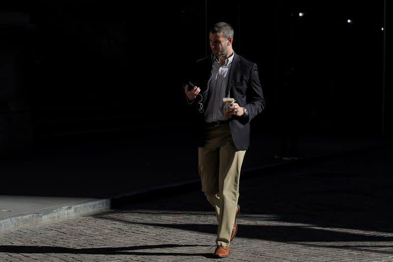 A man uses his phone on Wall St. outside the NYSE in New York