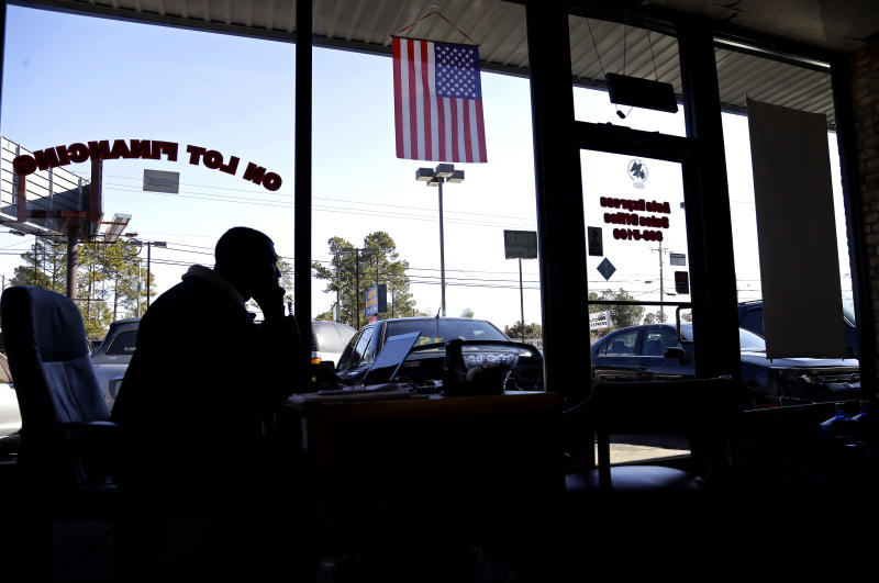 In this Monday, March 4, 2013 photo, salesman Donnie Alford talks on the phone in his office at Auto Express in Fayetteville, N.C. The auto and wheels business is located on Yadkin Road, near a main entrance to Fort Bragg military base. More than 8,500 civilian employees on the base will be furloughed one day a week starting in late April, the equivalent of a 20-percent pay cut, possibly affecting small businesses near the base. (AP Photo/Gerry Broome)