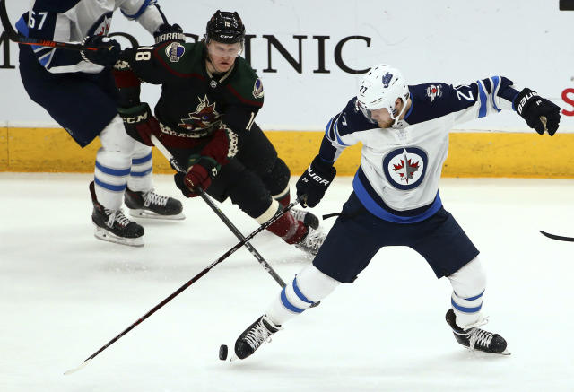 Winnipeg Jets left wing Nikolaj Ehlers (27) kicks the puck as Arizona Coyotes center Christian Dvorak (18) closes in during the second period of an NHL hockey game Saturday, April 6, 2019, in Glendale, Ariz. (AP Photo/Ross D. Franklin)