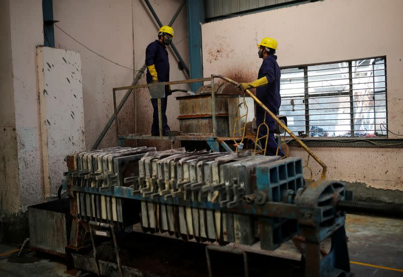 Workers stand next to a lead desulphurisation machine at ACE Green recycling Inc in Ghaziabad