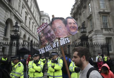 Demonstrators hold placards during a protest outside Downing Street in Whitehall, central London, Britain April 9, 2016. REUTERS/Neil Hall