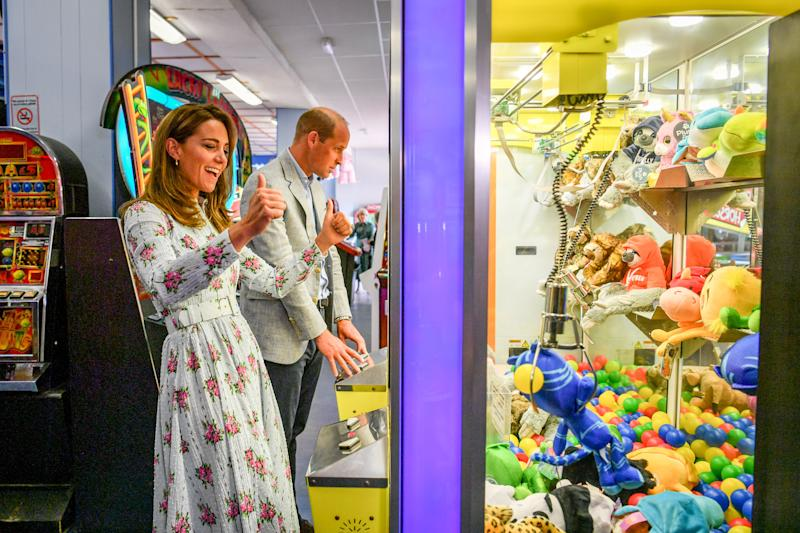 The Duke and Duchess of Cambridge play a grab a teddy game as the Duchess picks up a blue toy and celebrates with thumbs up, only for it to slip from the claws before reaching the winning chute, during their visit to Barry Island, South Wales, to speak to local business owners about the impact of COVID-19 on the tourism sector.