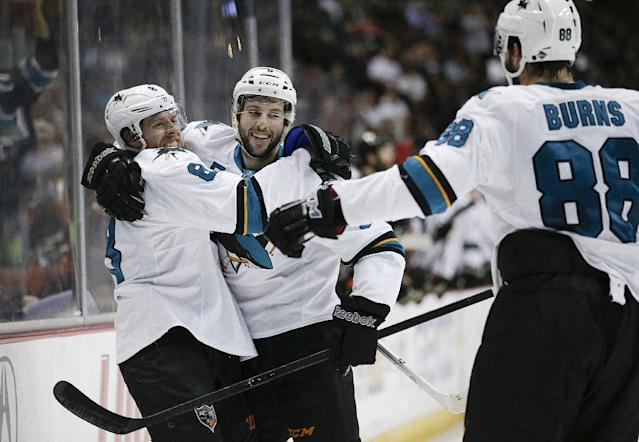 San Jose Sharks' Jason Demers, center, celebrates his goal with Joe Pavelski, left, and Brent Burns during the first period of an NHL hockey game against the Anaheim Ducks on Wednesday, April 9, 2014, in Anaheim, Calif. (AP Photo/Jae C. Hong)