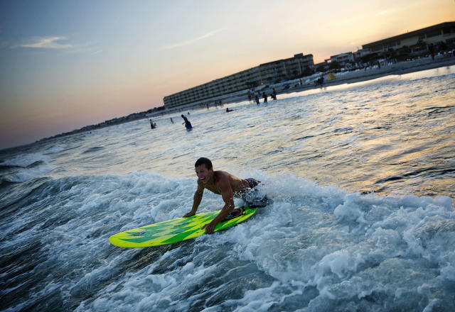 <p>Chad Riner, of Folly Beach, S.C., pushes his board through a wave while paddling back out into the surf, June 16, 2015, in Folly Beach. (AP Photo/David Goldman) </p>