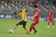 Australia's Aziz Behich, left, and China's Jingdao Jin fight for possession during a FIFA World Cup qualifying game in Doha, Qatar, Thursday, Sept. 2, 2021. (AP Photo/Hussein Sayed)