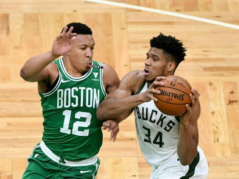 Milwaukee star Giannis Antetokounmpo drives to the basket against Boston's Grant Williams in the Bucks' NBA season-opening loss to the Celtics