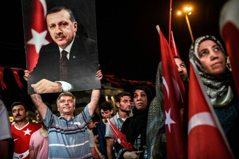 A man holds up a photo of Turkey's President Recep Tayyip Erdogan during a pro-Erdogan rally in Istanbul on July 22, 2016