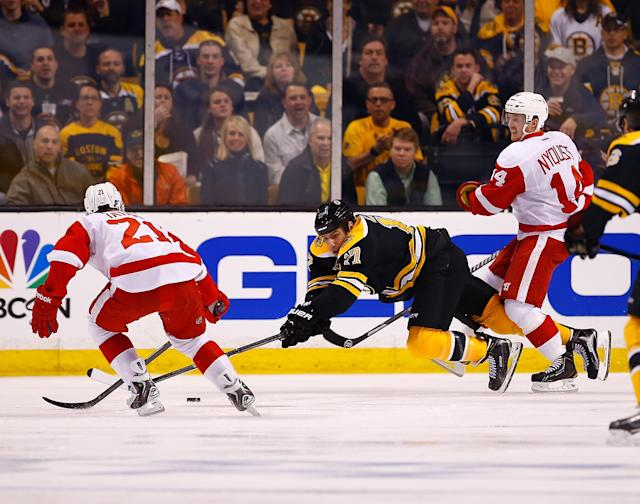 BOSTON, MA - APRIL 18: Milan Lucic #17 of the Boston Bruins is tripped up while reaching for the puck in front of Gustav Nyquist #14 of the Detroit Red Wings in the first period in Game One of the First Round of the 2014 NHL Stanley Cup Playoffs at TD Garden on April 18, 2014 in Boston, Massachusetts. (Photo by Jared Wickerham/Getty Images)
