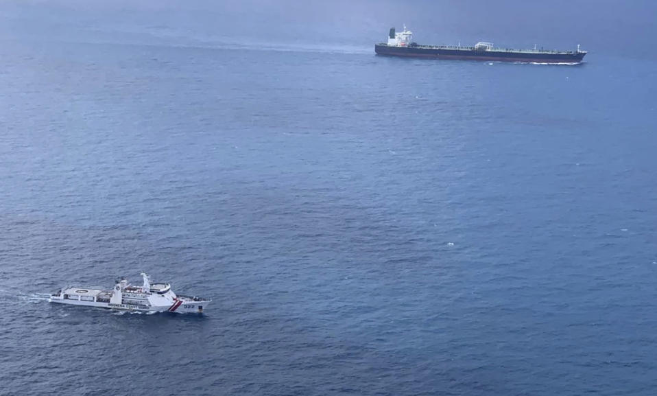 In this undated photo released by Indonesian Maritime Security Agency (BAKAMLA), a BAKAMLA ship escorts Iranian-flagged tanker MT Horse, top right, as they sail towards Batam Island, Indonesia. Indonesian authorities detained the crews MT Horse and Panamanian-flagged MT Freya that were seized Sunday for illegally transferring oil in Indonesian waters, an official said Tuesday. (Indonesian Maritime Security Agency via AP)
