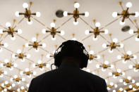 A cameraperson wearing a headset is silhouetted by ceiling lights as he records a remote video press conference by Chinese Foreign Minister Wang Yi held on the sidelines of the annual meeting of China's National People's Congress (NPC) in Beijing, Sunday, March 7, 2021. (AP Photo/Mark Schiefelbein)