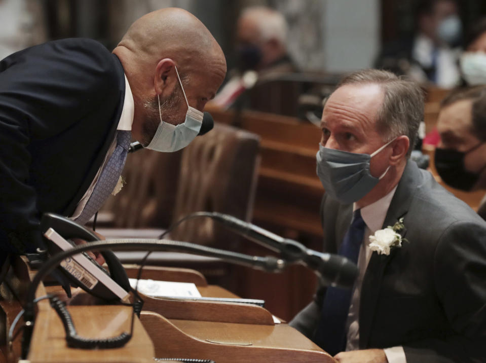 FILE - In this Jan. 4, 2021, file photo, Wisconsin Assembly Majority Leader Jim Steineke, R-Kaukauna, left, talks with Wisconsin Assembly Speaker Robin Vos, R-Rochester, during the first 2021-22 legislative session in the Assembly Chambers at the Wisconsin State Capitol in Madison, Wis. Wisconsin Gov. Tony Evers has issued a new statewide mask order an hour after the Republican-controlled Legislature voted to repeal his previous mandate on Thursday, Feb. 4, 2021. The Democrat Evers said in a video message Thursday that his priority is keeping people safe and that wearing a mask was the most basic way to do that. (Amber Arnold/Wisconsin State Journal via AP, File)