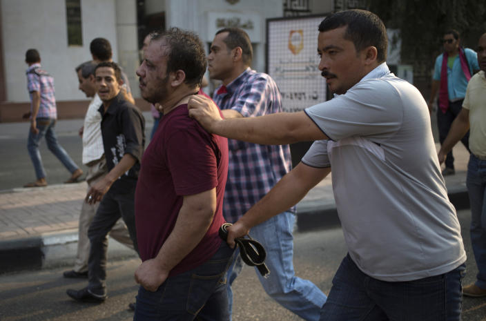 FILE - In this Sunday, Oct. 6, 2013 file photo, Egyptian security forces detain a wounded, suspected supporter, center, of ousted President Mohammed Morsi during clashes in Cairo, Egypt. Egypt's crackdown on Islamists has jailed 16,000 people over the past eight months in the country's biggest round-up in nearly two decades, according to previously unreleased figures from security officials. Rights activists say reports of abuses in prisons are mounting, with prisoners describing systematic beatings and miserable conditions for dozens packed into tiny cells. (AP Photo/Hassan Ammar, File)