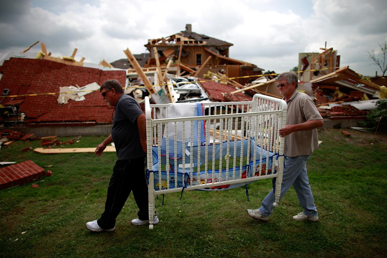 Mike Enochs (L) and Gary Enochs (R) salvage a baby crib from Mike Enochs' destroyed home after a tornado on April 4, 2012 in Forney, Texas. Multiple tornadoes touched down yesterday across the Dallas/Fort Worth area causing extensive damage.  (Photo by Tom Pennington/Getty Images)