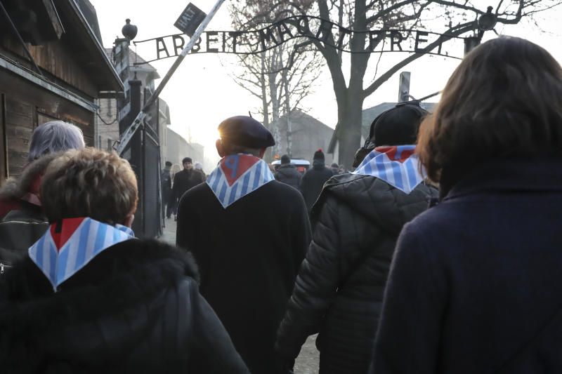 Survivors and their relatives walk through the gates of the Auschwitz Nazi concentration camp to attend the 75th anniversary of its liberation in Oswiecim, Poland, Monday, Jan. 27, 2020. (AP Photo/Czarek Sokolowski)