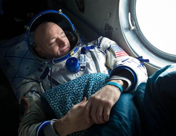 Expedition 26 commander Scott Kelly, wearing a turquoise wristband in honor of sister-in-law Gabrielle Giffords, looks out the window of a Russian Search and Rescue helicopter before the two hour helicopter ride to Kustanay, Kazakhstan shortly