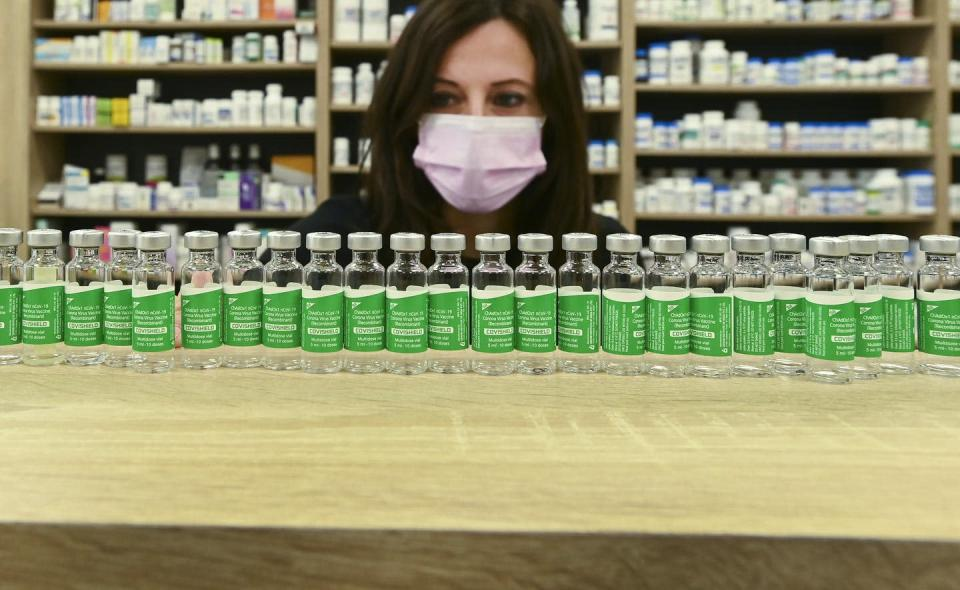 """<span class=""""caption"""">Pharmacist Barbara Violo arranges all the empty vials of the AstraZeneca COVID-19 vaccine that she has provided to customers at an independent pharmacy in Toronto. </span> <span class=""""attribution""""><span class=""""source"""">THE CANADIAN PRESS/Nathan Denette </span></span>"""