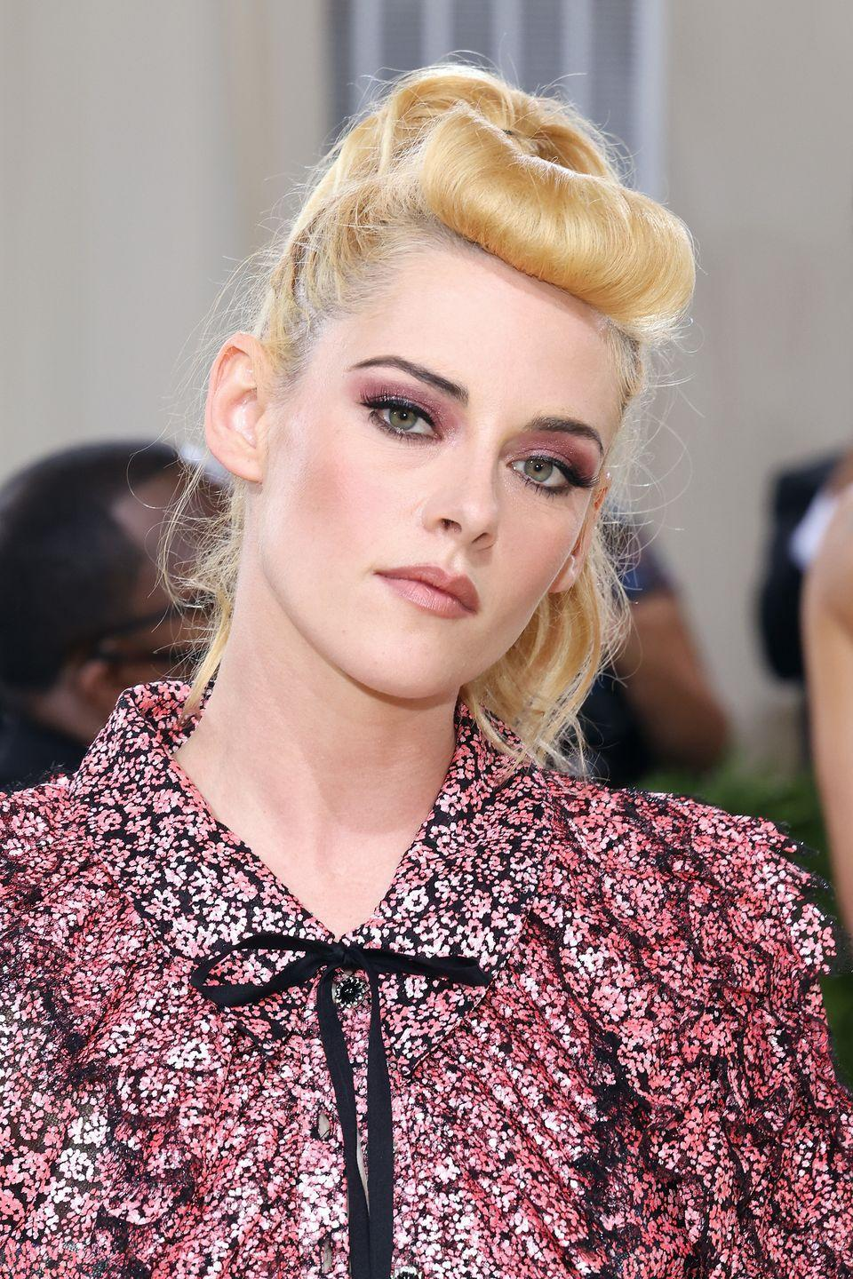 <p>Kristen Stewart nailed Fifties pin-up vibes with her 'bumper bangs' and high ponytail. Matching her dress, her make-up was a pink feat by Jillian Dempsey, who also gave Stewart a sharp arched brow and chiseled cheeks.</p>