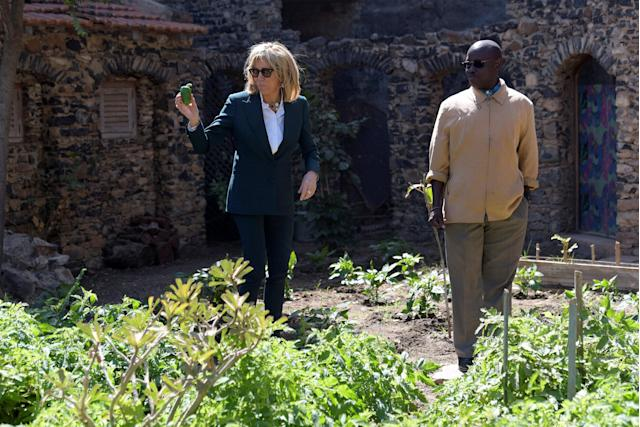 Brigitte Macron, the wife of the French president, holds a pepper as she visits the garden of a nursery school on Goree island, once a west African slaving post, off the coast of Dakar, Senegal, February 2, 2018. REUTERS/Seyllou/Pool