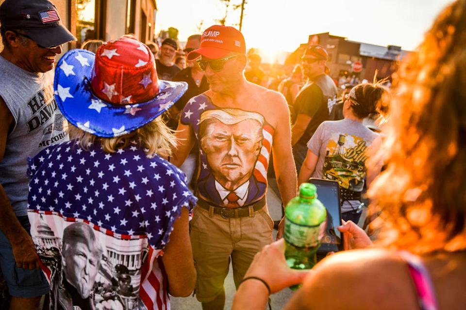 A South Dakota supporter walks down Main Street showing off his chest painted with a portrait of President Donald Trump. Source: Getty