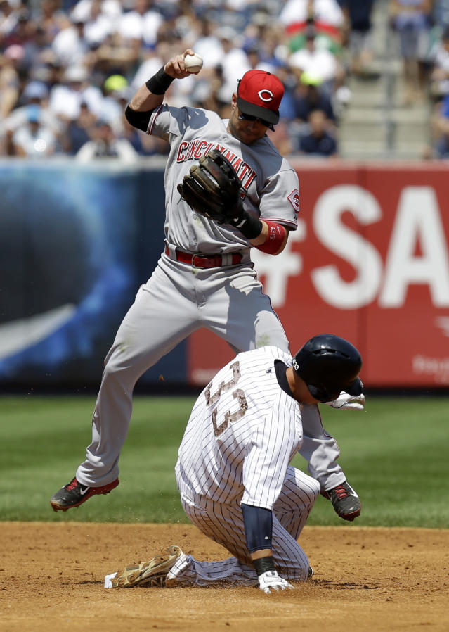 New York Yankees' Kelly Johnson, bottom, breaks up a double play attempt by Cincinnati Reds second baseman Skip Schumaker during the third inning of the game at Yankee Stadium Sunday, July 20, 2014 in New York. (AP Photo/Seth Wenig)