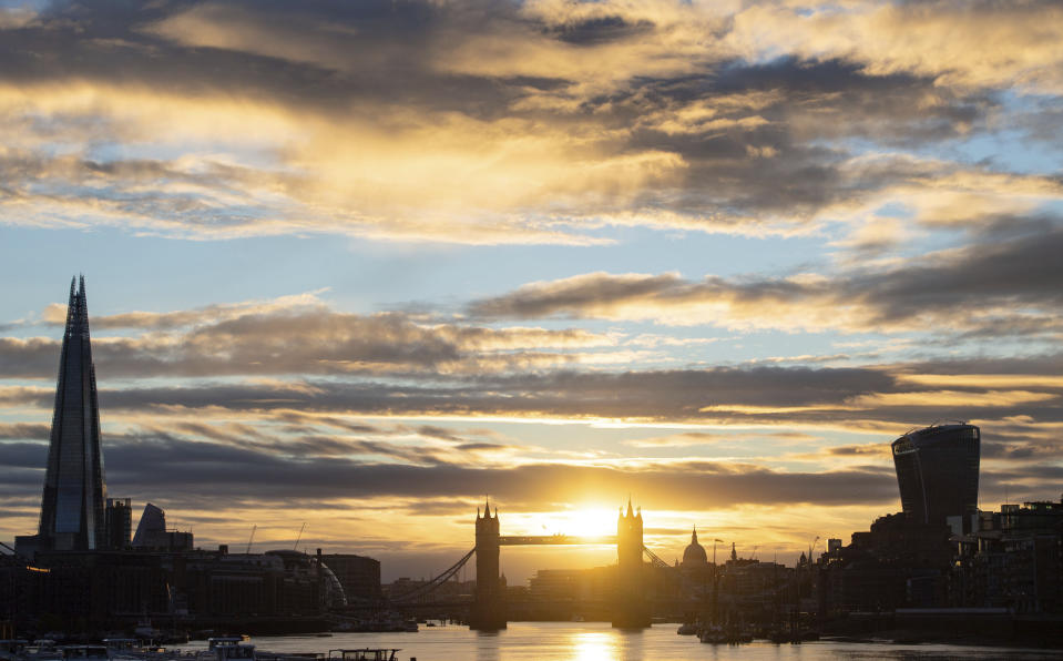 The sun sets behind the London skyline, including from left, the Shard, Tower Bridge, the dome of St Paul's Cathedral and 20 Fenchurch Street (also known as the Walkie Talkie) as the warm weather continues, in London, Wednesday, Aug. 5, 2020. (Dominic Lipinski/PA via AP)
