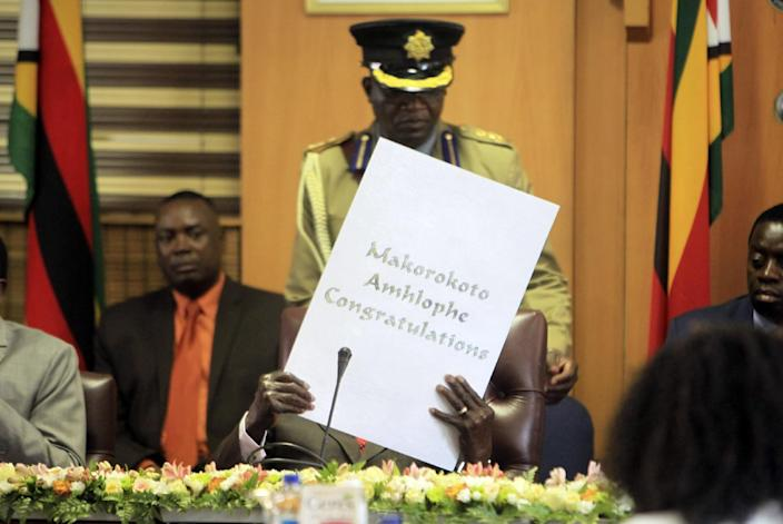 """Zimbabwe's President Robert Mugabe reads his birthday card as he marks his 93rd birthday at his offices in Harare, Tuesday, Feb. 21, 2017. Mugabe described his wife Grace, an increasingly political figure, as """"fireworks"""" in an interview marking his 93rd birthday. (AP Photo/Tsvangirayi Mukwazhi)"""