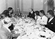 """<p>On August 3, 1934, this photo was captured at the annual board meeting for """"the post mortem club."""" According to the book <em>Death Warmed Over: Funeral Food, Rituals, and Customs from Around the World, </em><a href=""""https://www.abebooks.com/servlet/BookDetailsPL?bi=30346944346"""" rel=""""nofollow noopener"""" target=""""_blank"""" data-ylk=""""slk:all members were present at the meeting"""" class=""""link rapid-noclick-resp"""">all members were present at the meeting</a>, including the skeletal remains of club president, J.M. McAdou. </p>"""