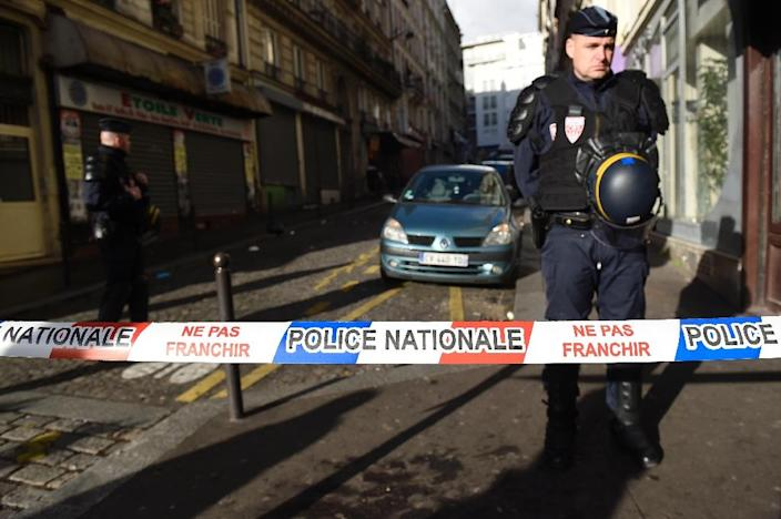French security forces cordon off a street after a man brandishing a meat cleaver was shot dead while trying to enter a police station in Paris, on January 7, 2016 (AFP Photo/Lionel Bonaventure)